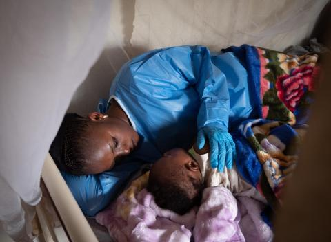 An Ebola survivor puts 6-month-old Josué to bed at a UNICEF-supported crèche in Beni, in eastern Democratic Republic of Congo.