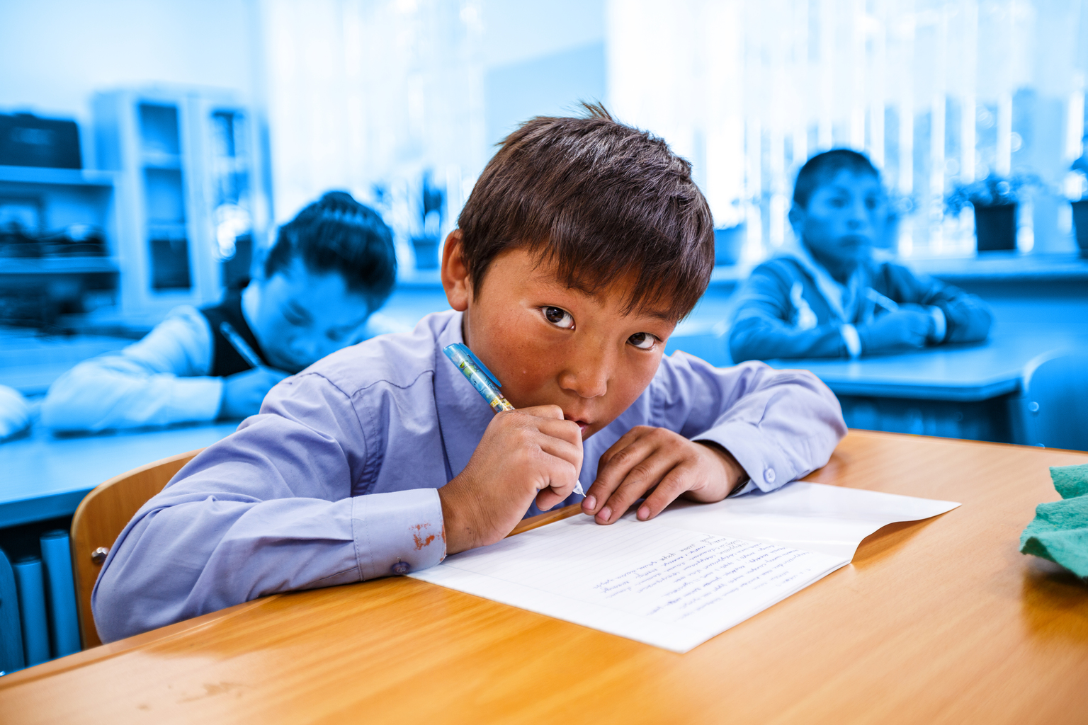 A boy looks the camera as he diligently writes down notes during class in Mongolia