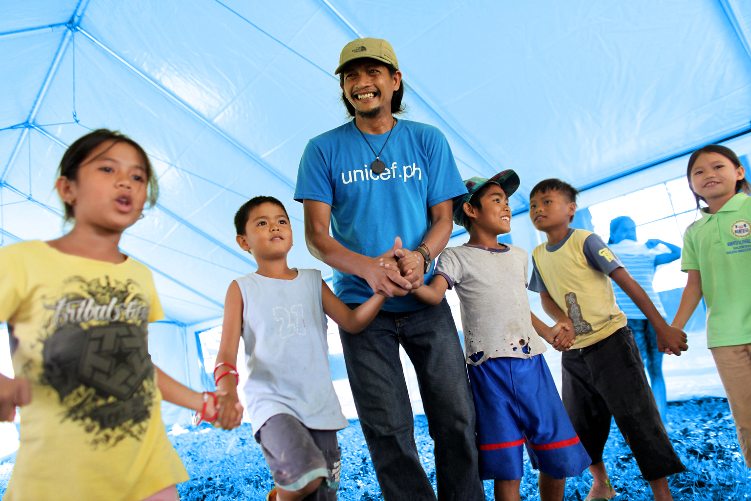a UNICEF worker plays with children at a child-friendly space