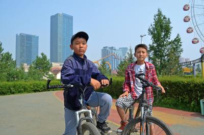 Two boys on their bikes look on