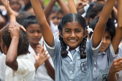 Girl in Fijian school raises her arm