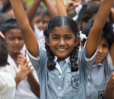 Girl smiling with her hands raised outside her school in Fiji