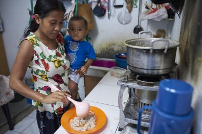 a mother dishes food for her baby in Timor-Leste