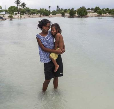 Taronga, 16, holds her two-year-old sister Teaborenga while standing in a flooded area in the village in Kiribati
