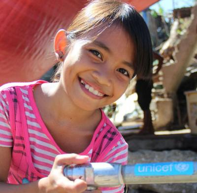 girl washing her hands with unicef supported tap