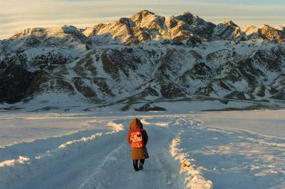 A first-grade student walks several kilometres to her home after school in the district of Altai in Mongolia through thick snow