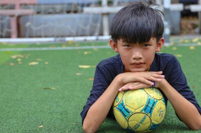 a boy poses for the camera leaning on a football