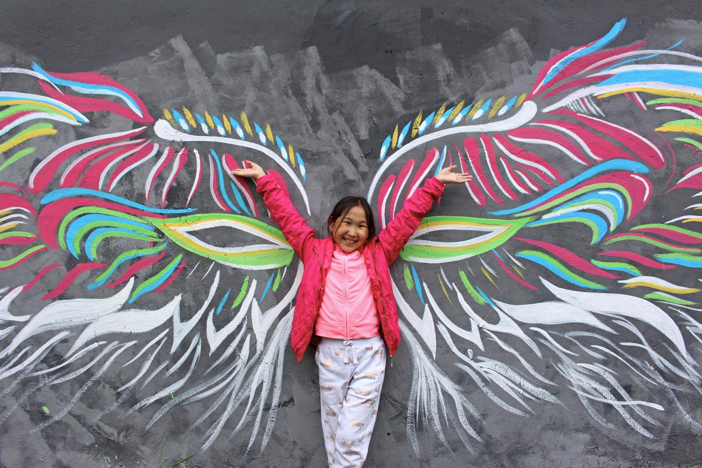 a girl raises her arms in front of drawings of wings on a wall