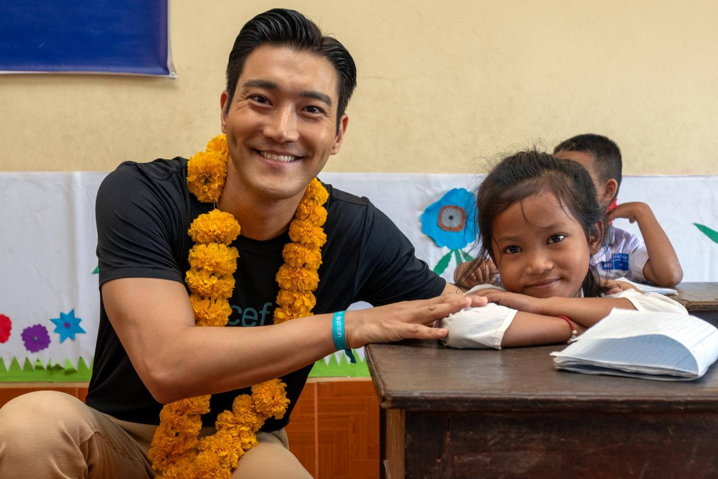 Siwon Choi smiles with a girl in a primary school in Laos