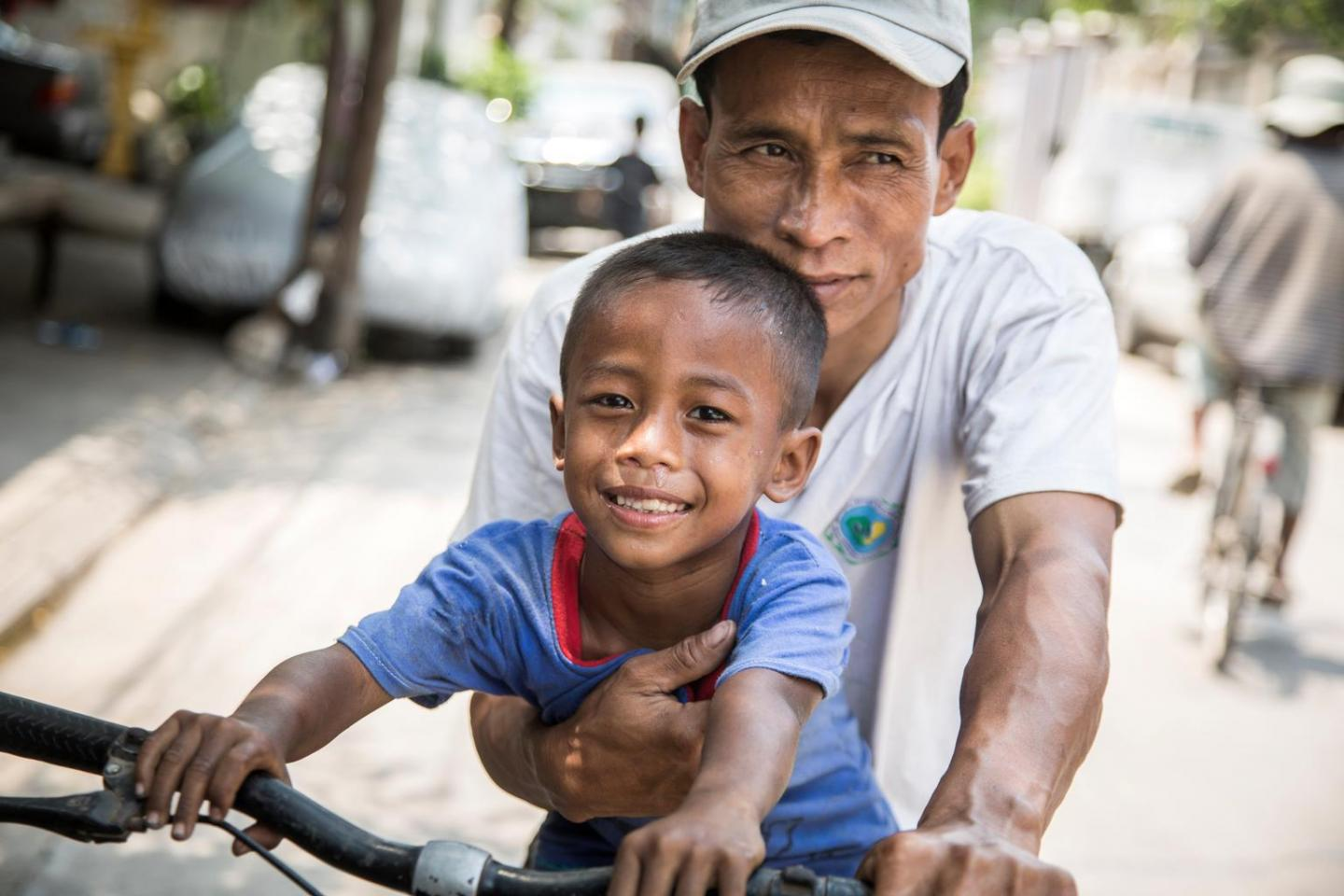 A boy with his father riding a bicycle through the city
