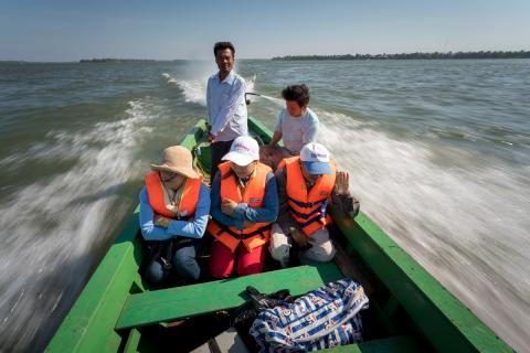 Health outreach workers speed along the Mekong River to deliver vaccines and prenatal care to a remote community in northeastern Cambodia