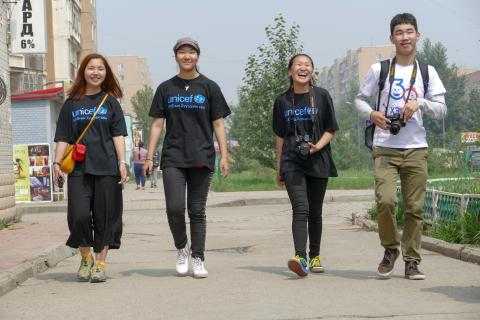 Four young photographers walk together smiling