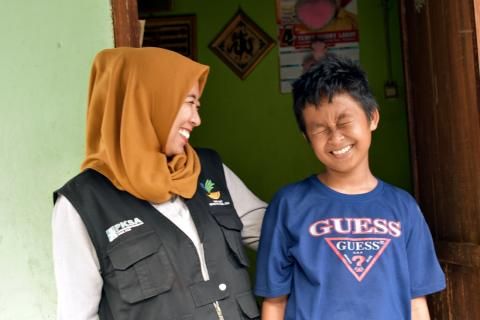 Social worker Chi Ramadhani stands with Rivaldi (13) outside the family home in Palu, Central Sulawesi