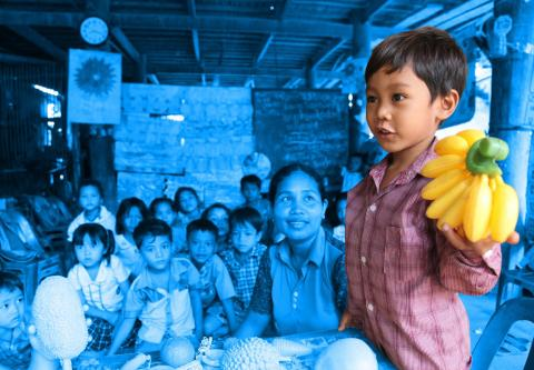 A child holds up plastic bananas during a class at a community pre-school in Cambodia
