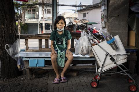 Chompuu, 10, sit next to her cart in Bangkok, Thailand where she sells juice.