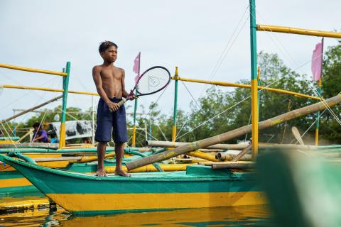 Allen Melecio, 13, stands on a boat posing with a tennis racket