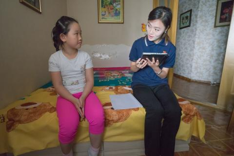 A survey member speaks to a child in her home