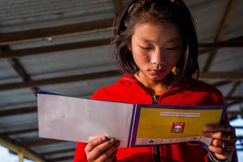 A girl  reads a cartoon book about landmine safety