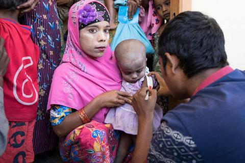 A Rohingya woman holds her little girl as her upper arm is measured to determine whether she is malnourished at a UNICEF-supported outpatient nutrition center in Thae Chaung village in Central Rakhine, Myanmar