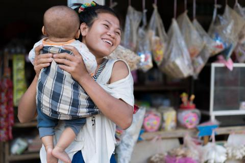 Mother Vandy, 25, lifts her 5 month old son in Sen Xay village, Vientiane province, Lao PDR