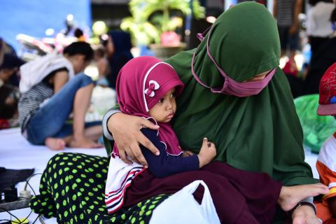 Fatimah, 2 years old, sits on her mother's lap in the evacuation tent yard of the RRI office, East Lolu, Palu City, Central Sulawesi.