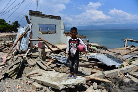 ido Saputra, 10 years old, stands in front of his home which was destroyed by a tsunami in Donggala Regency, Central Sulawesi.