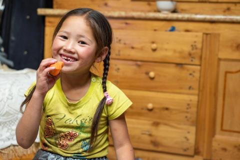 A girl in Mongolia eats a carrot