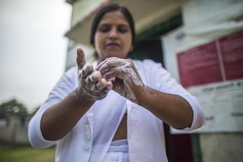 An Auxiliary Nurse Midwife (ANM) washes her hands before she examines a pregnant woman as part of Village Health and Nutrition Day (VHND) in Shrawasti, Uttar Pradesh.