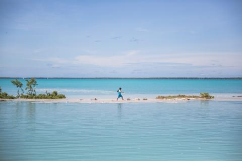 a boy walks from school to his house in Aberao village in South Tarawa, Kiribati