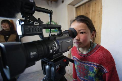 a girl in mongolia looking through a video camera