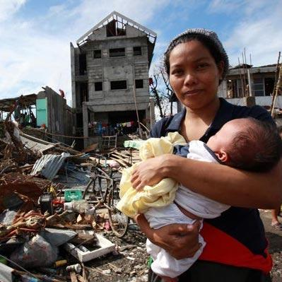 woman cradling a baby stands amid debris and other destruction caused by Super Typhoon Haiyan, in Tacloban City