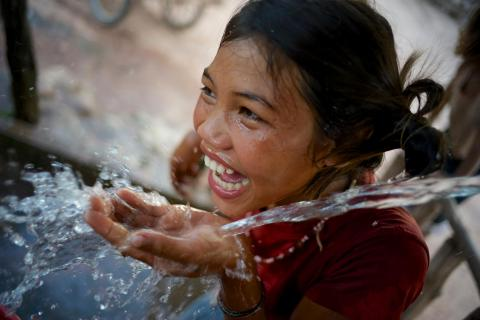 A girl smiles while drinking water at a water point in the village of Adone, Ta Oi District, Saravane Province. The village is home to the Pacoh ethnic group.
