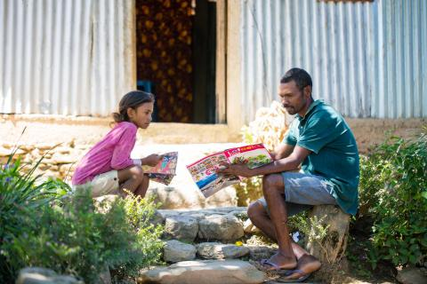 Joaquim de Jesus Mendonca (50) help his daughter Cristina Elena Mendonca (10) on school assignment that she got during the Covid lockdown. In Fahiria, Aileu, Timor-Leste.