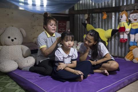 Vo Thi Thu Ngan, 13, sits with her mother Thach Thi So Pha and her younger sister Vo Thi Thu Ha, 9