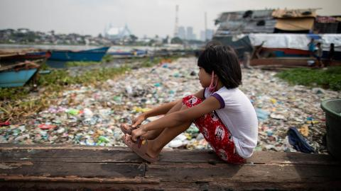 A girl sits on a piece of wood in Manila in October 2020; the longer children stay out of school, the less likely they are to return.