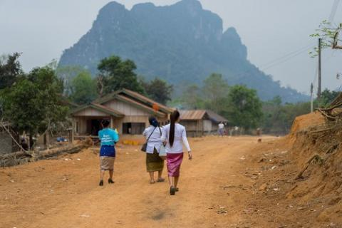 Health workers walk through a village in Laos to deliver vaccines