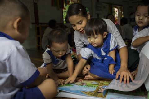 A teacher reads a local language text book to children in Myanmar
