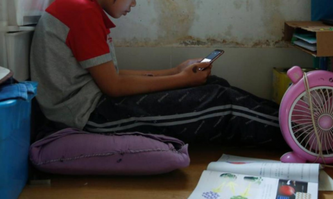 Secondary school student Wendy attends an online class with a smartphone at home during the novel coronavirus disease (COVID-19) outbreak