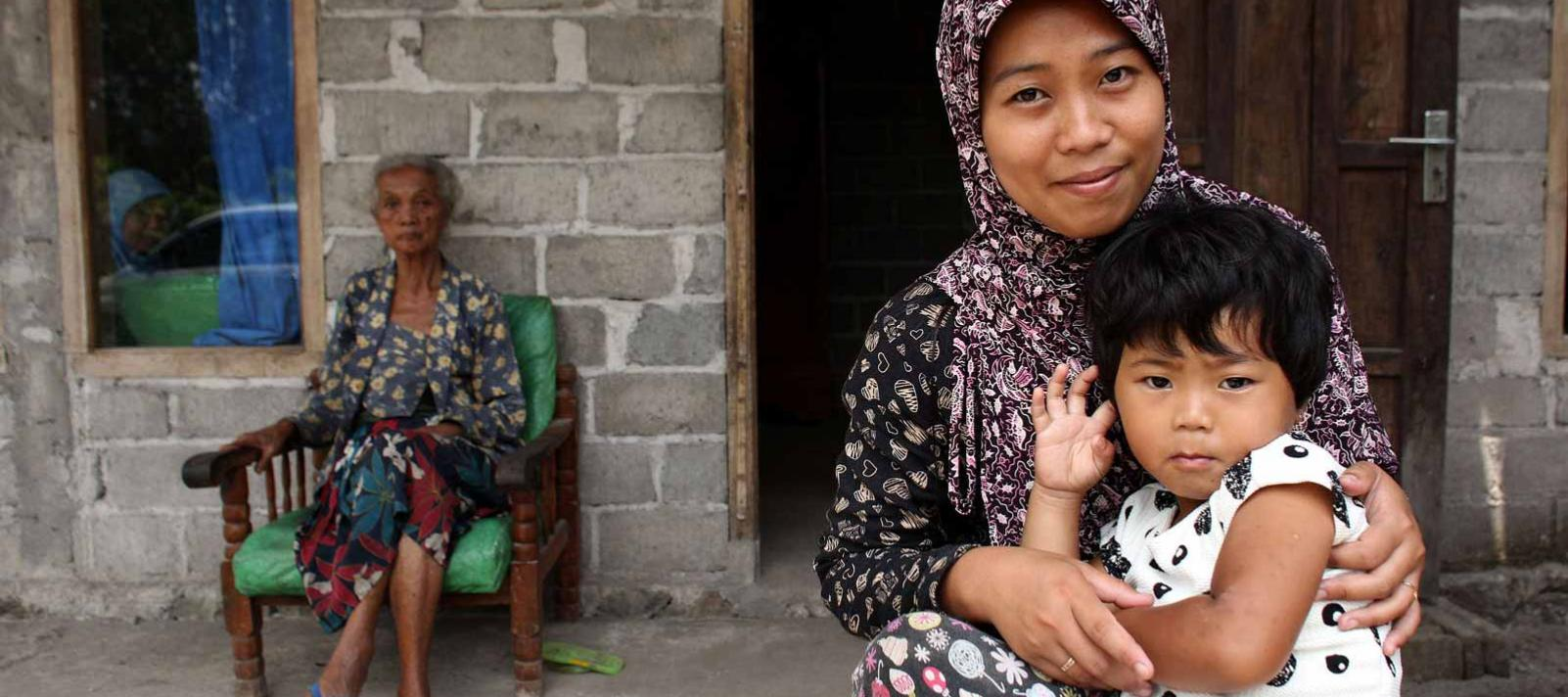 Rita Iriati, her 3-year-old daughter, Novita, on her lap, sits smiling near the entrance to their home, in the village of Kemalang in Klaten District, Central Java Province, Indonesia