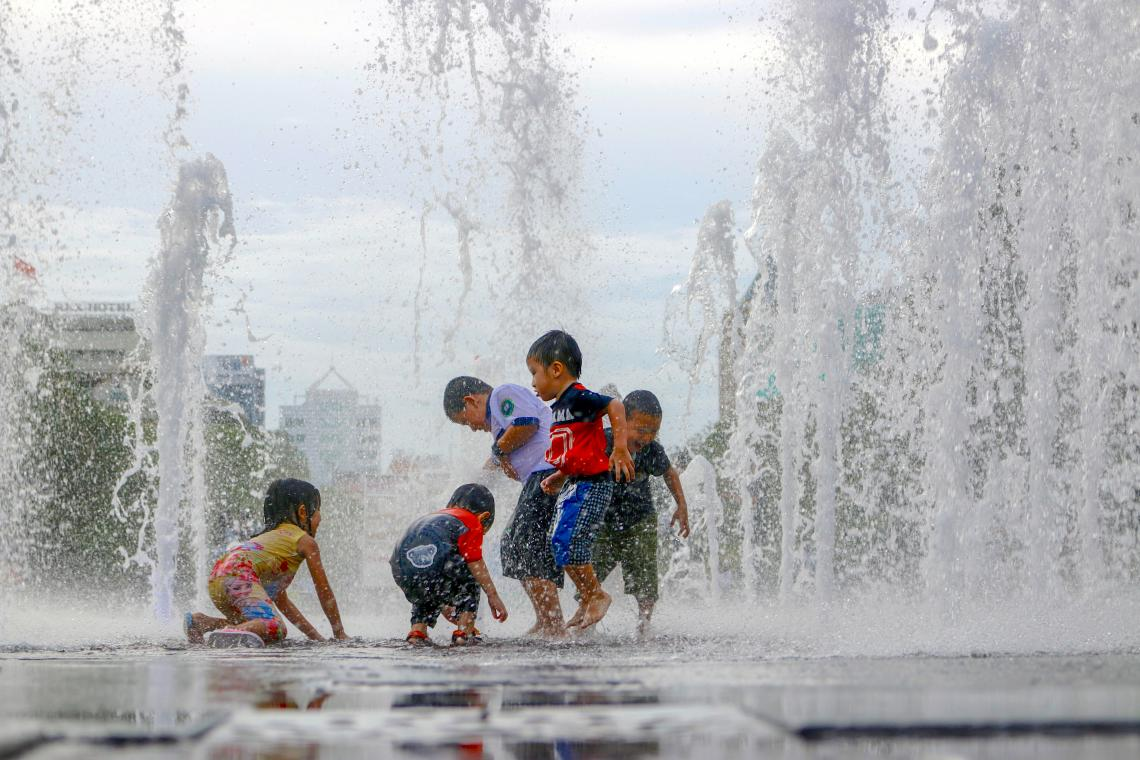 Children play in water fountains