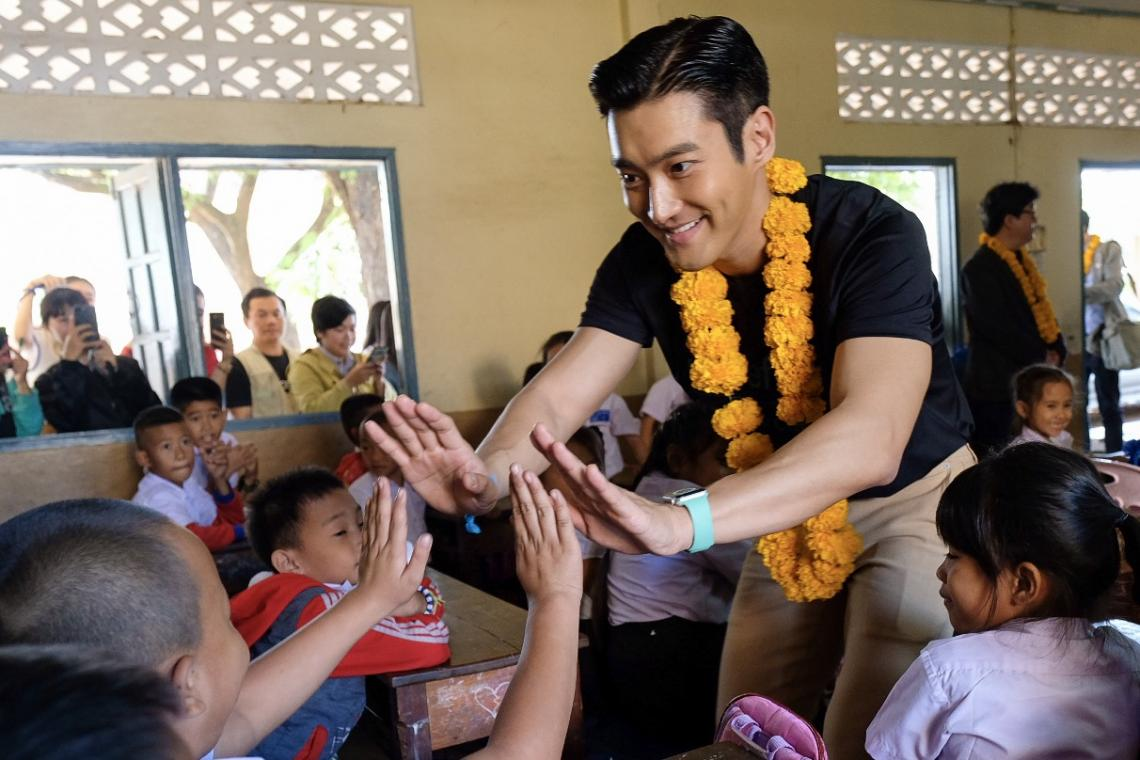 Siwon Choi high-fives some children in primary school in laos supported by UNICEF