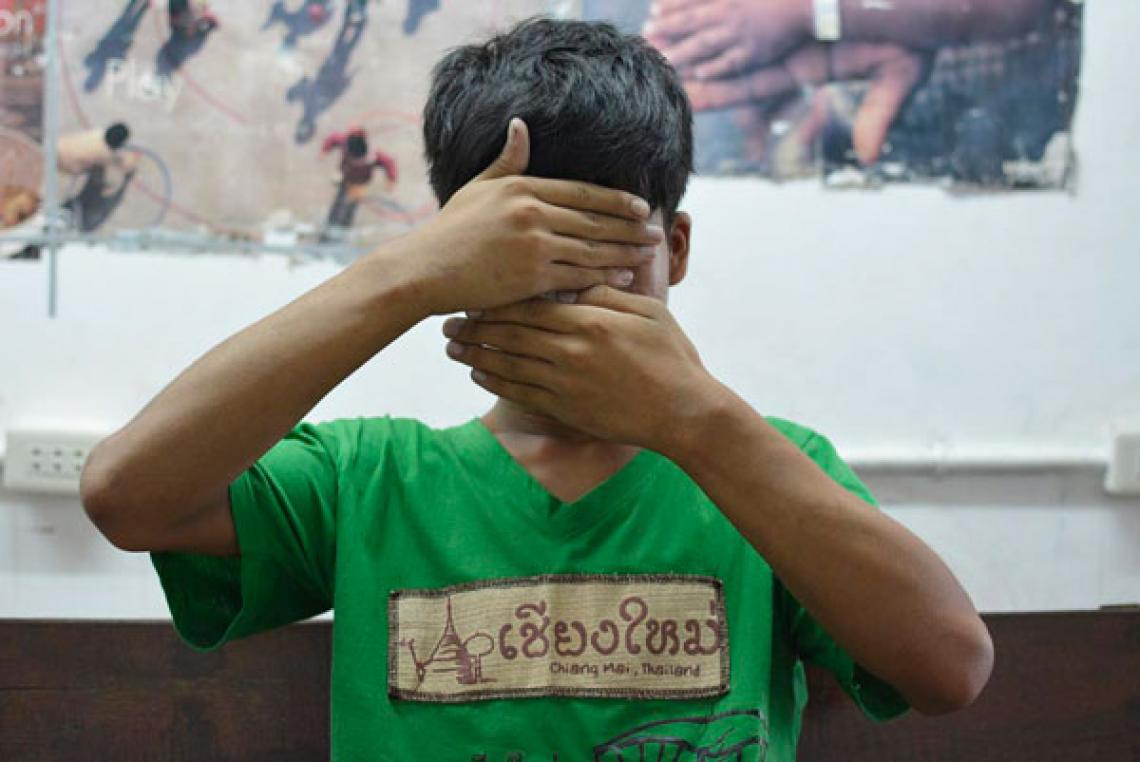 An at-risk adolescent covers his face in Chiang Mai, Thailand