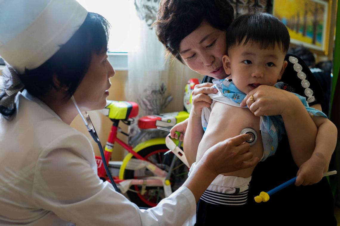 Dr Ju Song Hui, a household doctor in Jongju City, DPR Korea, checks on the health of two year old Jang