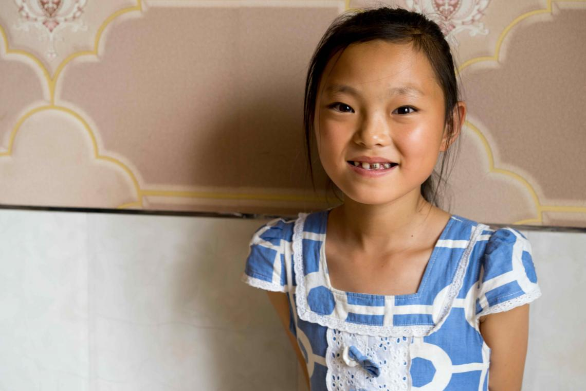 Yun Rye Yong, 10, smiling in her living room