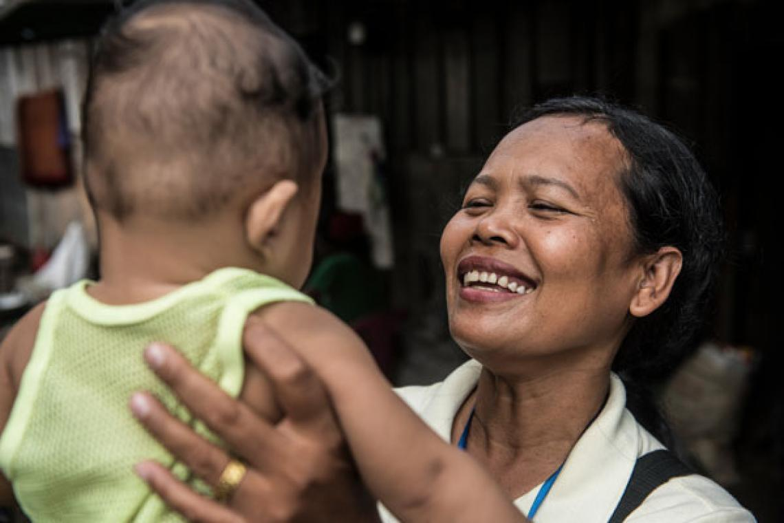 social worker picks up a child, smiling