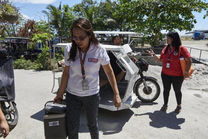 Health workers from Lower Bicutan Health Centre use a tricycle to visit a poor neighbourhood in Taguig City. The Philippines. 26 March 2019.