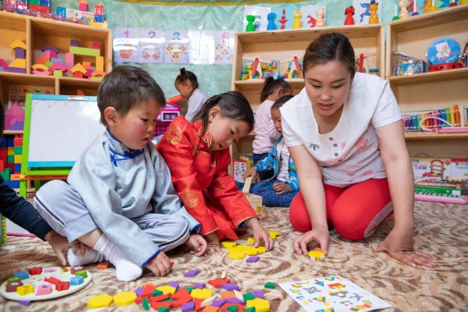 cousins Anar, 4, and Nandin-Erdene, 5, and a teacher play with puzzle blocks in the newly opened mobile 'ger' (traditional nomadic tent) kindergarten in Mongolia