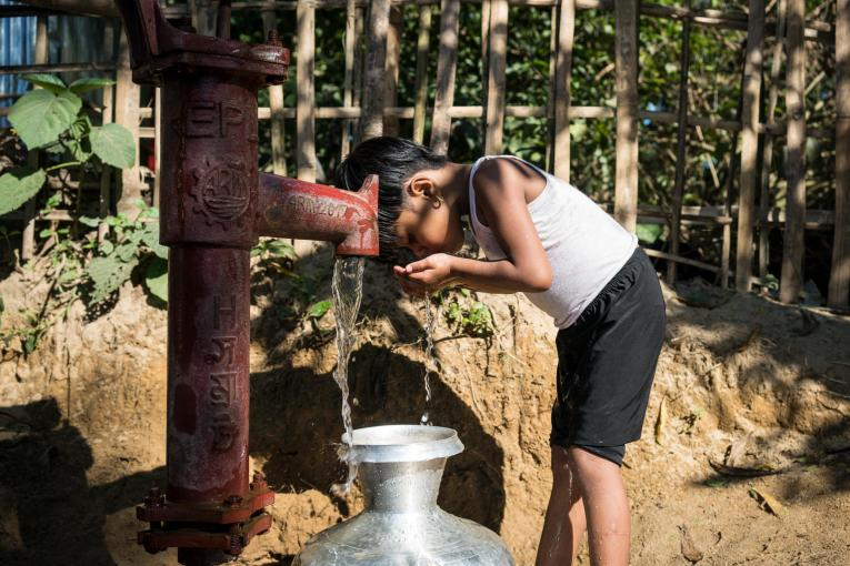 a young Rohingya girl drinks clean water from a water tap