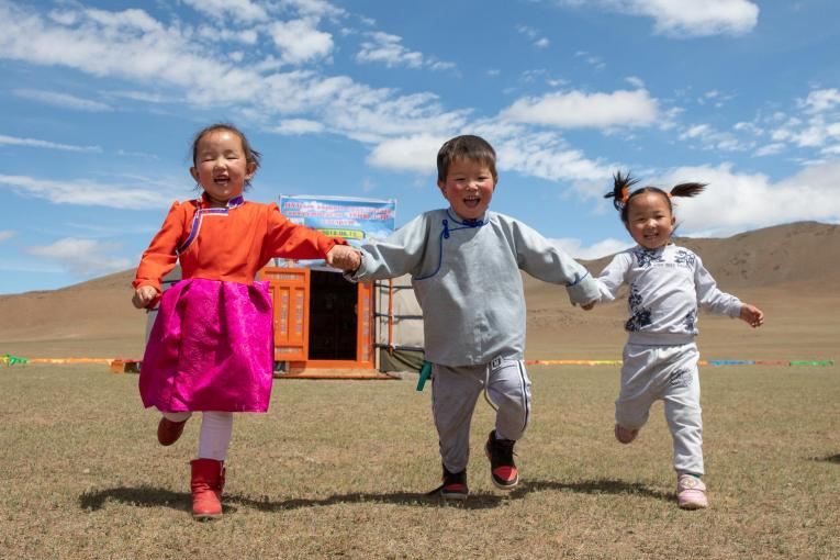 three laughing children run hand-in-hand outside the newly opened mobile 'ger' (traditional nomadic tent) kindergarten in Mongolia