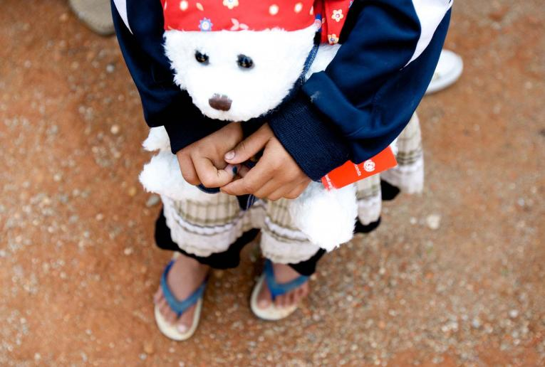 A girl who is HIV-positive holds a teddy bear in Ruili City, Yunnan Province.